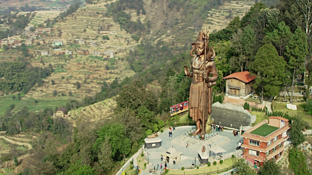 Aerial shot circles around the massive Kailashnath Mahadev Statue, the world's tallest Hindu Shiva statue. Terraced farms and green hills surround the statue in the background.